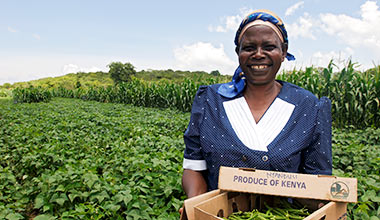 A farmer in Kenya proudly shows a box of her produce