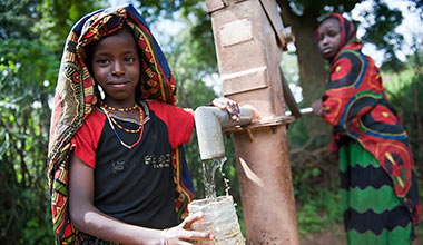 A young girl collects water at a village water pump