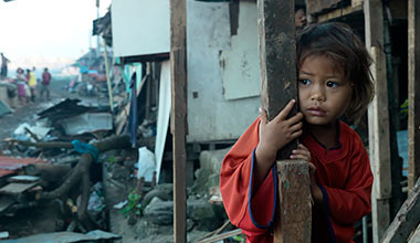 A young girl looks out over the devastation of her home town after Typhoon Haiyan