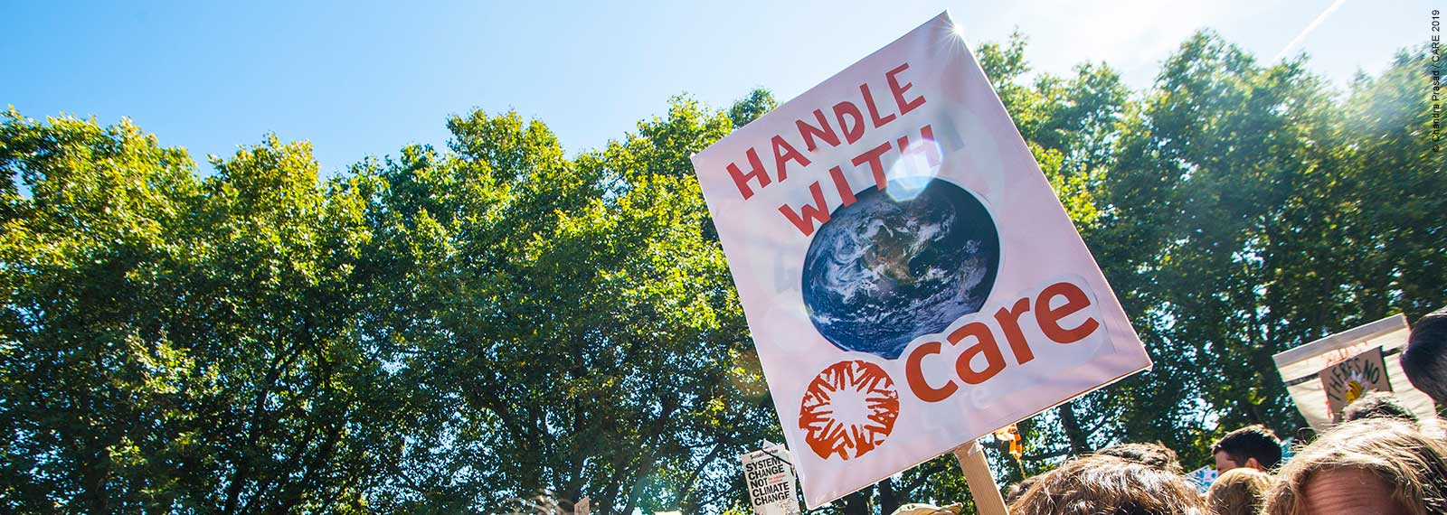 Handle with CARE placard at climate action protest