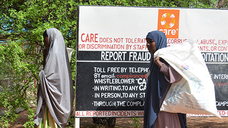 Women queuing in front of CARE sign