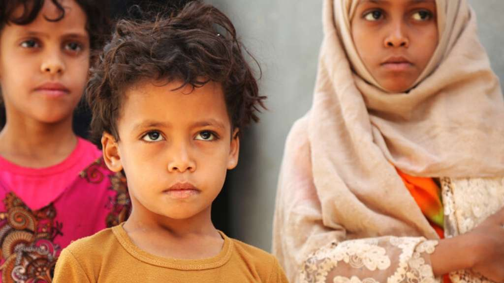 Three Yemeni children stand together in a refugee camp.