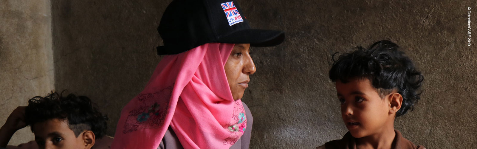 A woman in Yemen wearing a UK Aid cap, with two boys