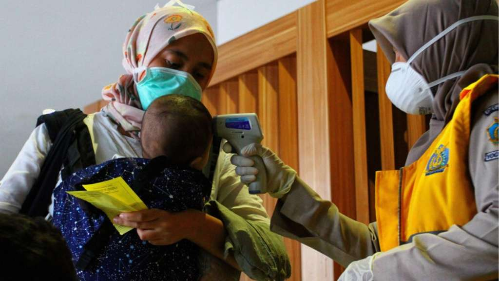 A child has their temperature taken by a health worker