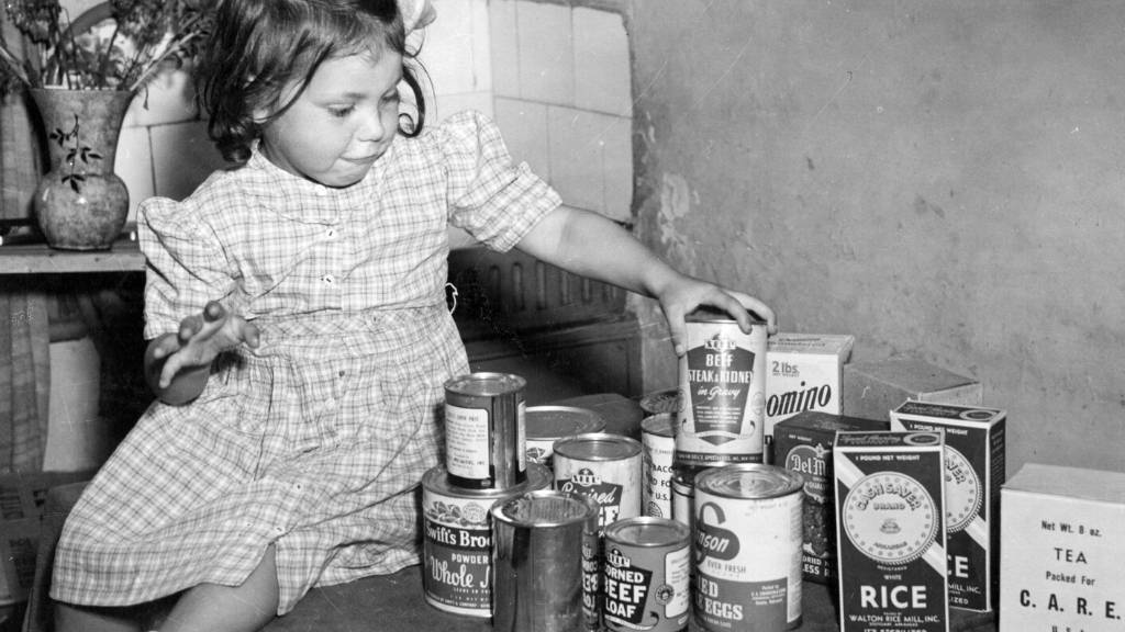 The 10,000th parcel. Frances Mason, 4 years old, examines with delight the contents of a CARE parcel sent to her widowed mother, UK.