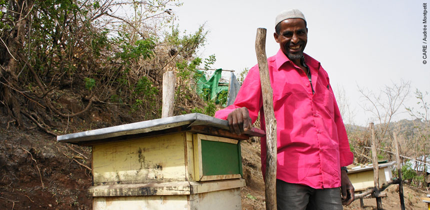 Ethiopian farmer Mohammed Abdule stands next to one of his hives. Training with CARE has allowed him to become less reliant on rainfall through beekeeping and more. © CARE / Audrée Montpetit