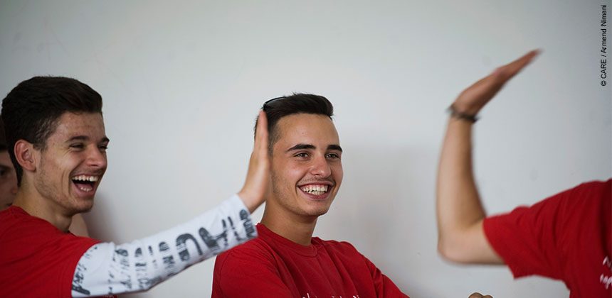 Boys sharing a 'high five' during a gender equality session at a school in Pristina