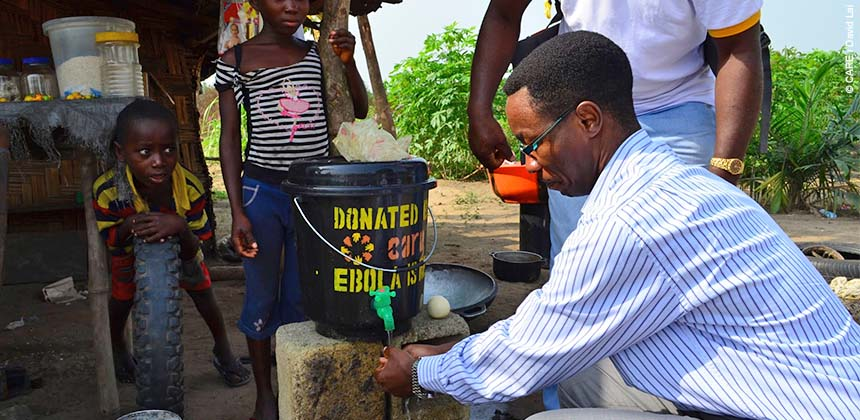 Public hand washing station at village in Liberia. Staff and community healthcare workers encourage people to consistently wash hands whenever leaving and entering a building or house