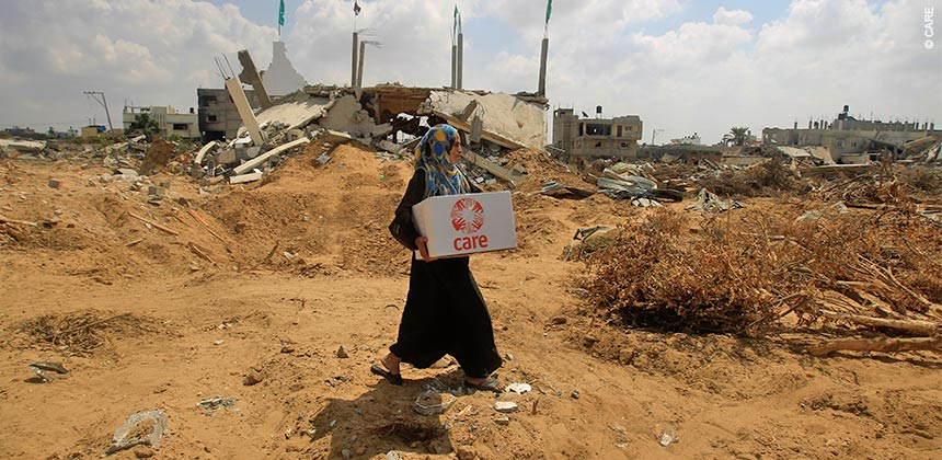 Um Ibrahim carries CARE's box of hygiene supplies home through the destruction caused by the war last July © CARE