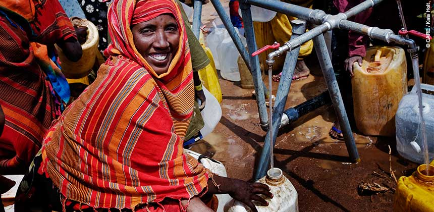 A newly arrived refugee from Somalia collects water in Dadaab last year. © CARE / Kate Holt