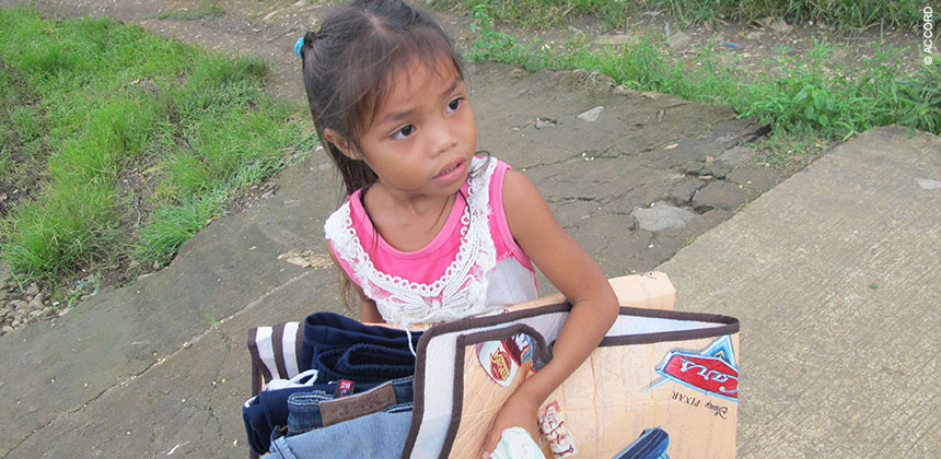 A girl helps her family prepare for Typhoon Hagupit © ACCORD
