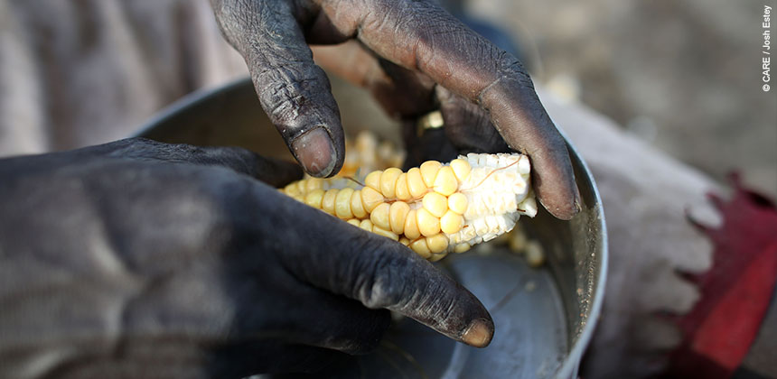 A woman preparing maize © CARE / Josh Estey