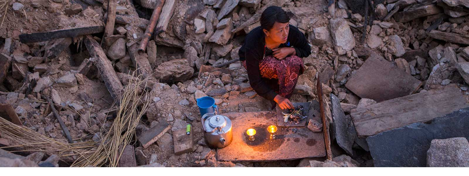 A woman lights candles in the ruins of her home after the Nepal earthquake