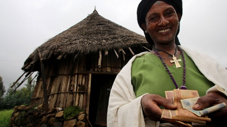 Fasika Altasbe holding the money she has earned since CARE started working with her