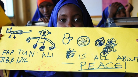 "Schoolgirl from Dadaab refugee camp holds up sign saying ""is all about peace"" for World Refugee Day 2014"