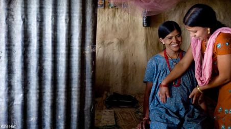 A health worker examines a pregnant woman in Nepal