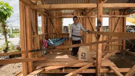 Man stands in his new home with storm-proof roof in the Philippines