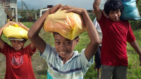 Children carrying CARE food packs home after a food distribution camp in the Philippines