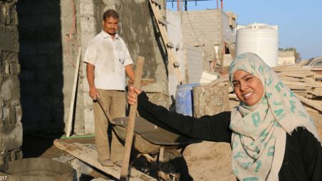 Woman and man constructing a building in Yemen