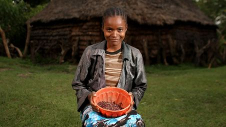 A woman in Ethiopia holding a bowl of beans