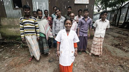 Health worker and group of men in Bangladesh