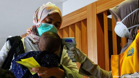 A child, held by their mother, has their temeprature taken by a healthworker, Indonesia.