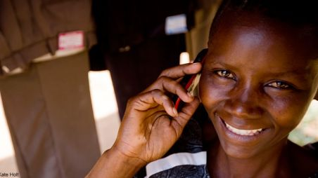 Lilian, a young entrepreneur in Kenya, holding a mobile phone