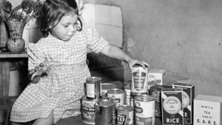 Girl with cans from CARE package