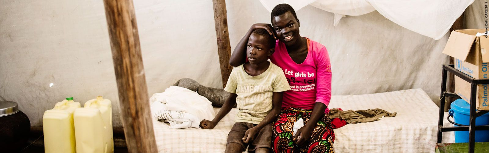 A teenage girl and her younger brother in a tent in a refugee camp in Uganda