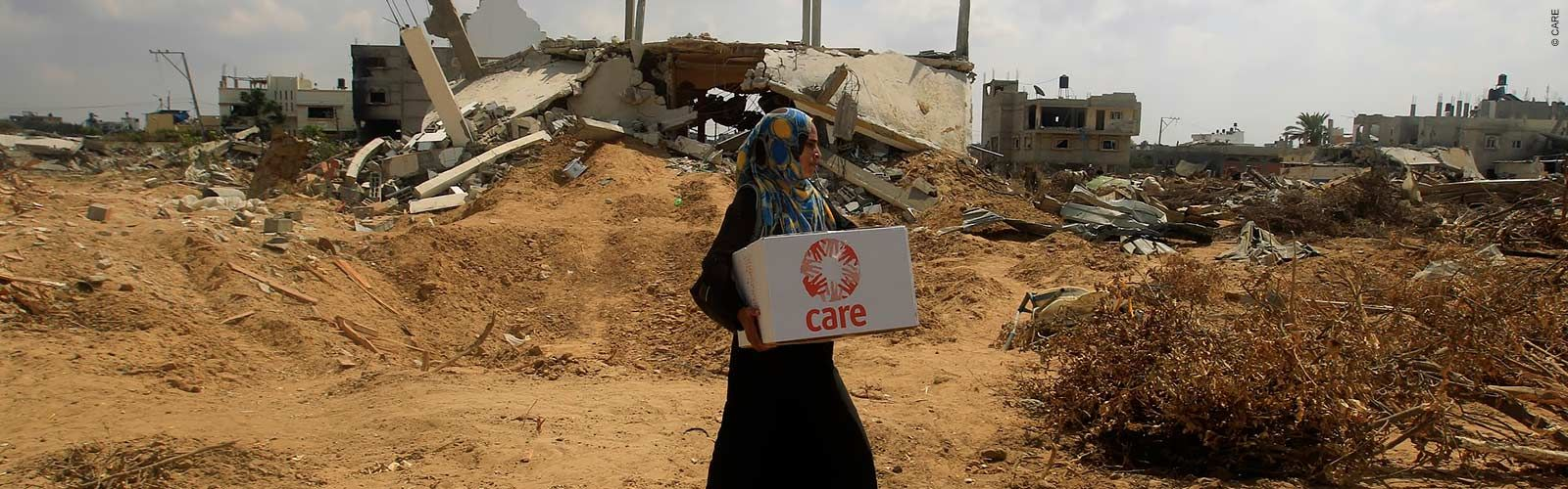 A woman carries a CARE package past destroyed buildings during the Gaza Crisis