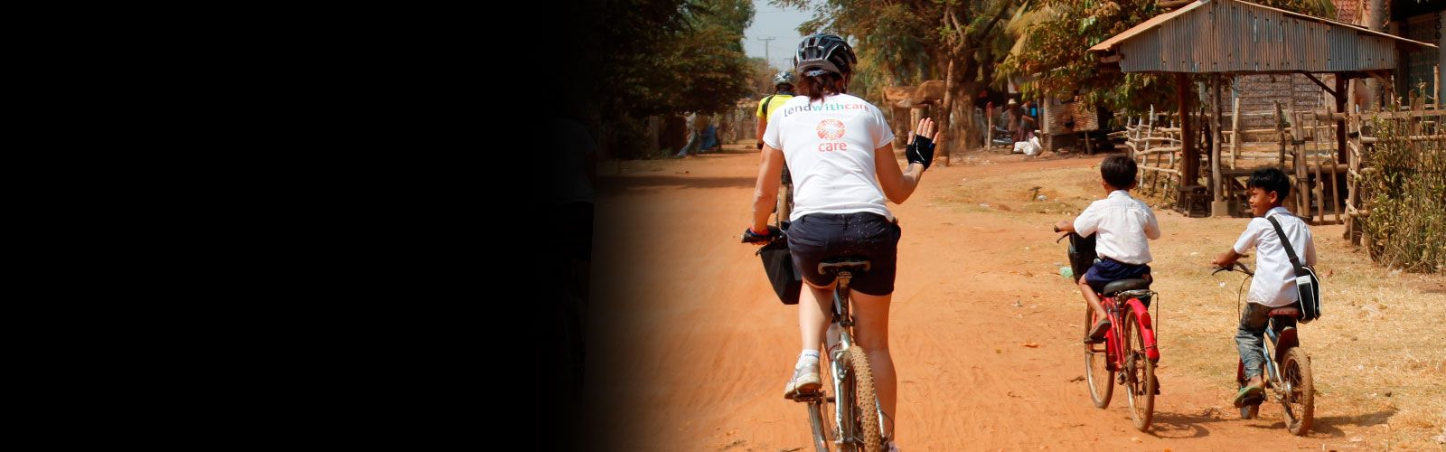 CARE supporter cycling in Cambodia and waving at young Cambodian children