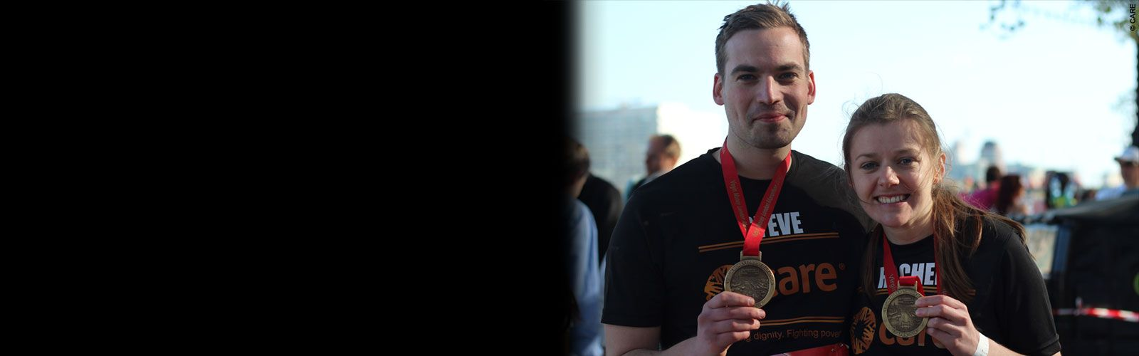 Two CARE runners smiling and holding their medals with pride at the end of the London Marathon