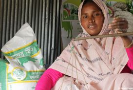 Harisa, a farmer in Bangladesh, weighing animal feed
