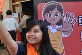 A young woman taking a selfie in front of a campaign banner