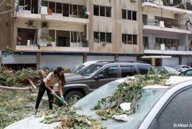 Woman clearing debris outside building in Beirut