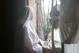 A Syrian refugee woman standing at a window