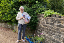 Ruth stand in her driveway with her flowers raising money for CARE