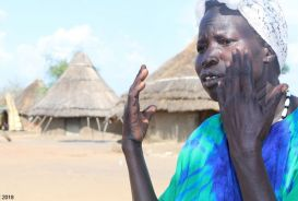 Mary Amal in front of village huts in South Sudan