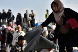 Woman shaking out a blanket in refugee camp