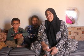 Woman with two children inside home at IDP camp in Syria
