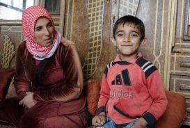 Mariam and her son inside their home