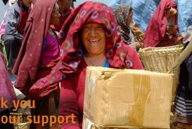 Thank you for your support: a woman receiving an aid package in Nepal © CARE