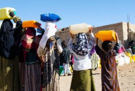 Women and girls in Amran City gather at a water tank provided by CARE