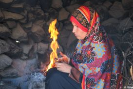 Kawather beside fire inside her home, Yemen