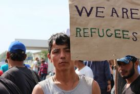 Refugees in Serbia line up in silent protest along the border with Hungary after the crossing was closed