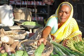 A woman displays food at her market stall in Chittagong South East Bangladesh © CARE