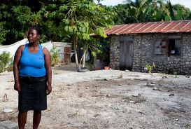 Mireille stands where her house used to be. She now lives in a temporary structure next door but is rebuilding her life with community microfinance. © CARE