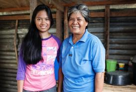 Jinky and her mother stand outside their home rebuilt with the help of CARE © CARE / Mario Ignacio