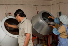 Maria Eugenia Calle Callizaya, right, an El Alto resident and recipient of CARE Bolivia's business training program, works with her husband, Severo Mamani, left, preparing chocolates in a kitchen at their home in El Alto, Bolivia