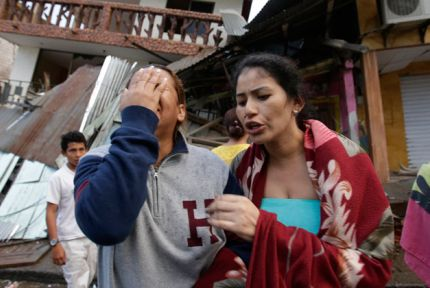 Women crying in the street in front of damaged house, Ecuador
